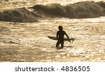 silhouette of a surfer at sunset - stock photo