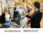 Small photo of Cashier Looking At Female Customer Making Payment