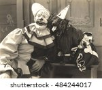 Small photo of Clown posing with dog dressed in clown costume