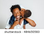 Small photo of An African American boy on the shoulders of his father, leans over to kiss him on the cheek. His father laughs with closed eyes.
