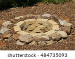 Small photo of Fire pit made of the yellow aluminous bricks and boulders surrounded by pebbles in the summer garden