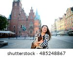 Small photo of Cheerful dark-haired girl-tourist stands on the square of the old town. Area is paved with stone. Discern the outlines of the beautiful old buildings and monument. Girl holds a guide and maps.