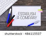 Small photo of Notebook with ESTABLISH A COMPANY Handwritten on wooden background and Modern Computer Keyboard. Top View Composition