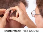 doctor fitting a senior man... | Shutterstock . vector #486123043