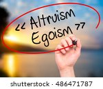 Small photo of Man Hand writing Altruism - Egoism with black marker on visual screen. Isolated on background. Business, technology, internet concept. Stock Photo