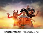 Stock photo happy brother and two sisters on halloween funny kids in carnival costumes outdoors cheerful 487002673