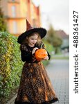 Small photo of Eve of All Saints' Day. Girl of younger school age portrays the evil enchantress. She is wearing a dark dress and a hat. In the hands of the girl Jack-o-lantern.Children adore Halloween.