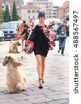 Small photo of Milan, Italy, 21 September 2016 - woman poses for photographers in faux fur coat with Afghan hound before GUCCI fashion show on Milan Woman Fashion Week street style Spring/Summer 2017