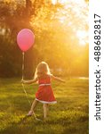 Small photo of Little girl in a red dress holding a balloon. Happy and carefree childhood.