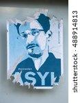 Small photo of JUNE 2016 - BERLIN: an image of Edward Snowden on an already faded sticker demanding granting him asylum in Germany, Berlin.