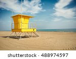 Small photo of Flowy white clouds above a sunlit yellow lifeguard post on an empty sandy beach near quiet sea