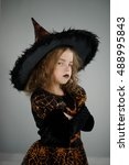 Small photo of All Hallows Eve. Beautiful girl 8-9 years in image the evil sorcerer. She is dressed in black and orange dress and a big hat. Girl tries to make an evil look. Trick or Treat. Children adore Halloween