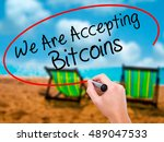 Small photo of Man Hand writing We Are Accepting Bitcoins with black marker on visual screen. Isolated on sunbed on the beach. Business, technology, internet concept. Stock Photo
