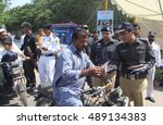 Small photo of KARACHI, PAKISTAN - SEP 26: DIG Traffic Police, Dr. Ameer Sheikh distributing pamphlets about awareness of car safety belts bikers helmets, at hotel Metropole road on September 26, 2016 in Karachi.