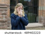 Small photo of Sick young woman blowing her nose on a tissue or handkerchief as she stands outdoors in town, conceptual of a seasonal flu epidemic or allergic rhinitis