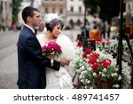 bride admires red flowers while ... | Shutterstock . vector #489741457
