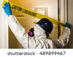 Small photo of Environmental abatement worker hangs lead hazard caution sign