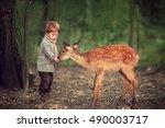 cute little boy is feeding a... | Shutterstock . vector #490003717