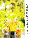 Small photo of Concept of herbal tea with honey and accessories. Camomile tea in a glass mug. Green meadow background. Light airy capture. Vertical