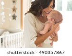 Stock photo young mother holding her baby in the bedroom 490357867