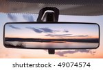 Sunset on a river, reflected in the rearviewmirror of a car - stock photo