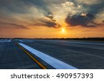 Small photo of Runway, airstrip in the airport terminal with marking in sunset background. Travel aviation concept.