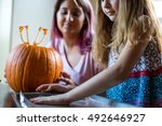 mother and daughter carving a... | Shutterstock . vector #492646927