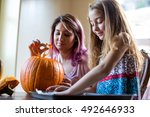mother and daughter carving a... | Shutterstock . vector #492646933