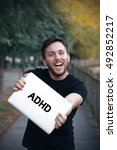 Small photo of Young man holding Adhd sign
