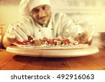 cook in kitchen with big wooden ... | Shutterstock . vector #492916063