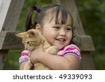 Adorable little asian girl giving her orange kitten a hug - stock photo