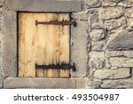 Small photo of Wooden trap door with rusty hinges - Rustic architecture background with a stone wall of a german house, with it's wooden trap door and the rusty hinges