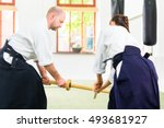 Small photo of Man and woman fighting with wooden swords at Aikido training in martial arts school