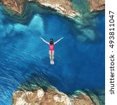 young women jumping off cliff... | Shutterstock . vector #493811047