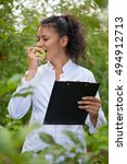 Small photo of smiling agronomist with notebook standing in apple orchard