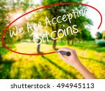 Small photo of Woman Hand Writing We Are Accepting Bitcoins on blank transparent board with a marker isolated over green field background. Business concept. Stock Photo