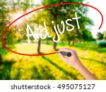 Small photo of Woman Hand Writing Adjust on blank transparent board with a marker isolated over green field background. Stock Photo