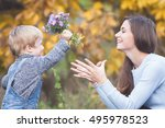 child gives to happy mother... | Shutterstock . vector #495978523