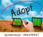 Small photo of Man Hand writing Adopt with black marker on visual screen. Isolated on sunbed on the beach. Business, technology, internet concept. Stock Photo