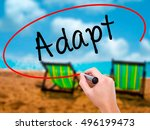 Small photo of Man Hand writing Adapt with black marker on visual screen. Isolated on sunbed on the beach. Business, technology, internet concept. Stock Photo