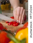 Woman working in the kitchen chopping up the vegetables. Female slicing pepper for salad. Close up chef cutting vegetables. - stock photo
