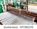 a row of textile looms weaving...