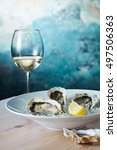 fresh oysters and a glass of... | Shutterstock . vector #497506363