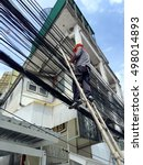 Small photo of Bangkok, Thailand - September 25, 2016: A technician connect Internet fiber optic FTTX cable to provide service to a house. This new technology is replacing ADSL.