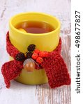 Small photo of Cup of tea with lemon wrapped woolen scarf, warming beverage for flu and cold, autumnal decoration of rowan, alder cone and acorn