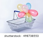 Small photo of concept of black friday advert sale empty metal shopping basket with colorful balloons set on background, close up