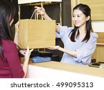 Young Female Asian Salesclerk...