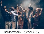 Small photo of Enjoying carefree time together. Group of beautiful young people throwing colorful confetti and looking happy