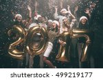 Happy New Year to you! Group of cheerful young people in Santa hats carrying gold colored numbers and throwing confetti
