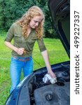 Small photo of Dutch woman investigates car oil level with dipstick